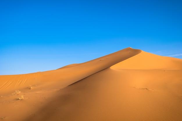 Mooi schot van een zandduin met een heldere blauwe hemel