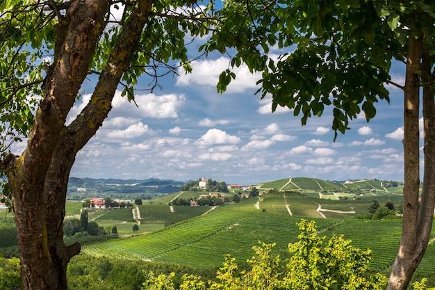Mooi schot van groene heuvels en gebouwen in de verte onder een blauwe bewolkte hemel