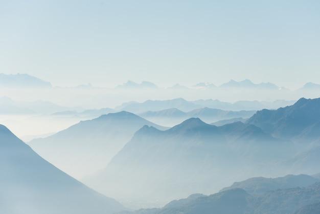 Mooi schot van hoge witte heuveltoppen en bergen bedekt met mist