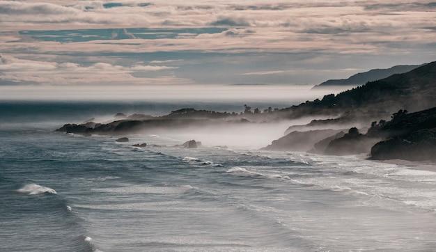 Mooi schot van mistige bergen en golven van de zee in de oceaan