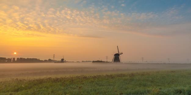 Mooi schot van molens in het veld met de zon stijgt in de