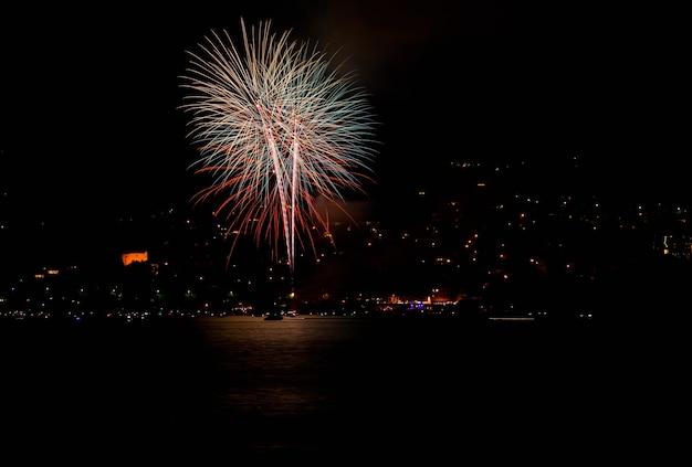 Mooi schot van rood vuurwerk boven een meer in zwitserland 's nachts