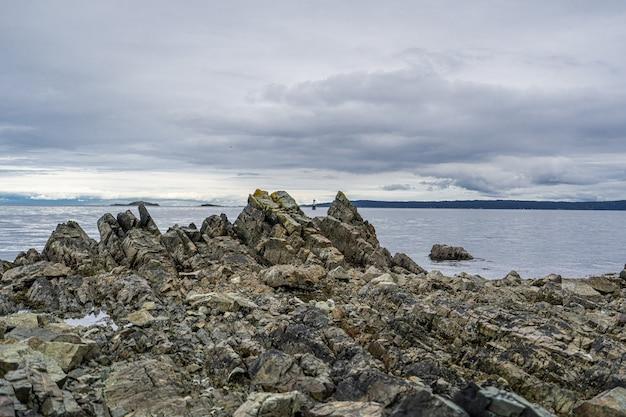 Mooi schot van rotsachtige klip dichtbij zee onder een hemel
