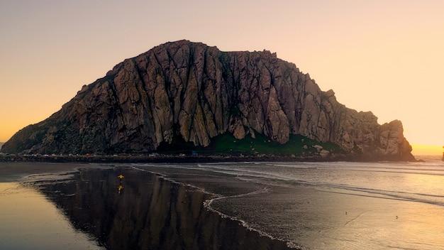 Mooi schot van rotsachtige klippen dichtbij een strand met zonlicht aan de kant