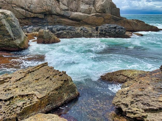 Mooi schot van rotsformaties in de buurt van de zee met gekke golven golven