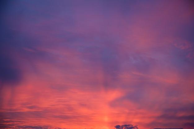 Mooi schot van roze wolken in een heldere blauwe hemel met een landschap van zonsopgang