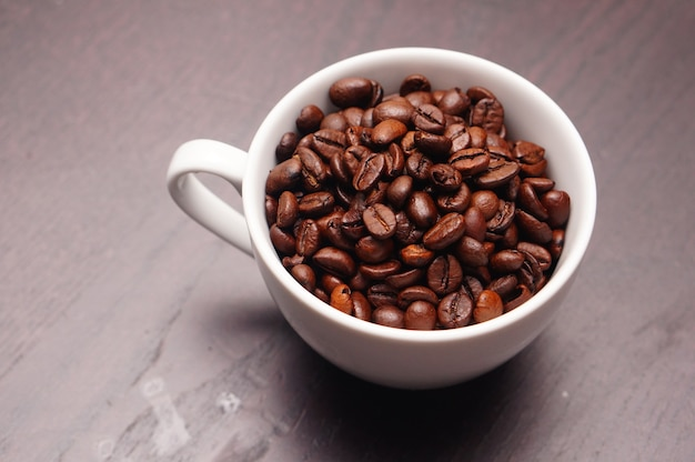 Mooi schot van witte kop vol koffiebonen op een houten tafel