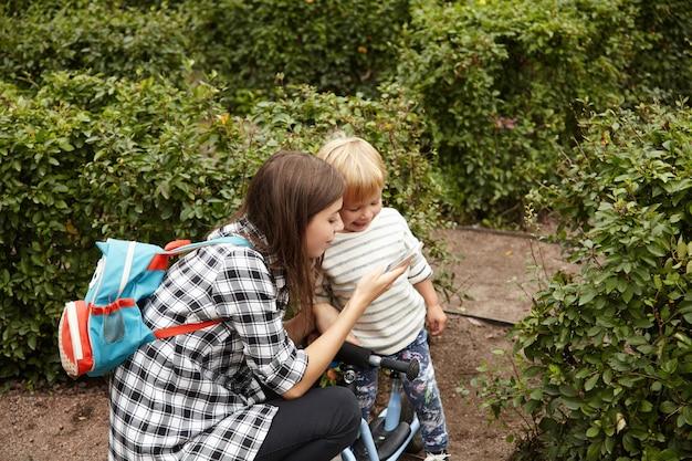 Mooi schot van zorgzame moeder die met haar zoon buiten loopt. jonge blanke vrouw foto's tonen aan haar baby op digitaal apparaat. mooie moeder in geruit overhemd met kinderachtige rugzak zittend op hunkers.