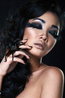 Mooi sensueel aziatisch meisje met spin in studio