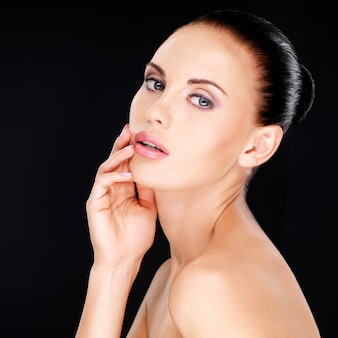 Mooi sensueel gezicht van de volwassen vrouw met frisse huid - op zwarte achtergrond