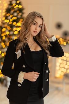 Mooi sensueel jong meisje in een elegant zwart pak en een blazer met weelderige borsten in een kamer met kerstversiering en gele lichten. kerstvakantie