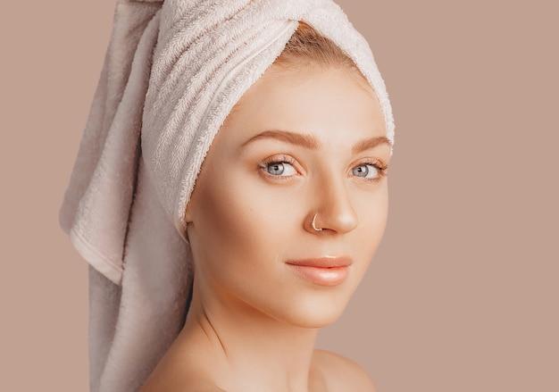 Mooi sensueel jong meisje met schone huid op een beige ondergrond