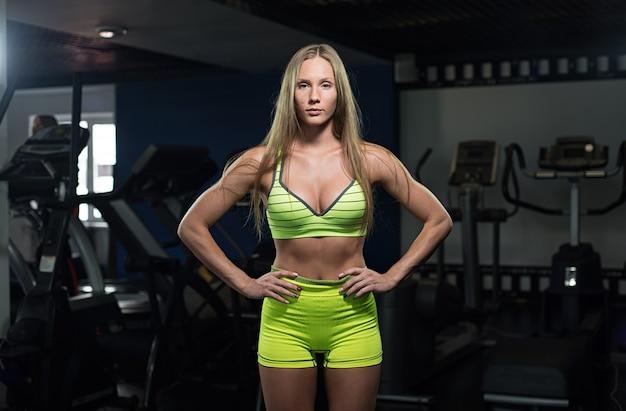 Mooi sexy atletisch gespierd jong meisje. het meisje stelt na een training.