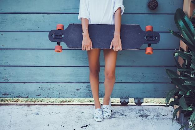 Mooi sexy jong meisje in korte broek met longboard in zonnig weer