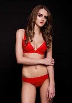 Mooi sexy meisje dat rode buitensporige lingerie op zwarte draagt