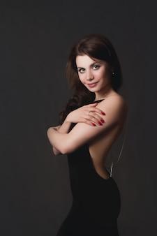 Mooi sexy meisje dat zwarte avondjurk draagt