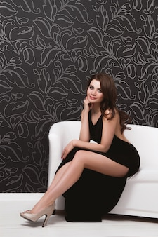 Mooi sexy meisje dat zwarte avondjurk op een witte bank draagt