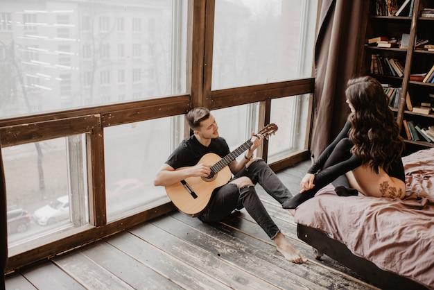 Mooi sexy meisje en haar vriend het spelen gitaar