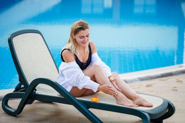 Mooi sexy meisje in een zwart zwempak zit bij het zwembad en brengt zonnebrandcrème aan op haar lichaam