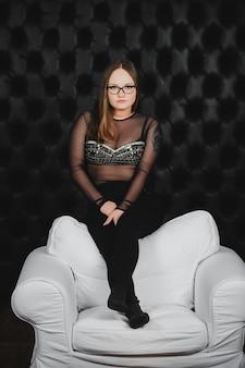 Mooi sexy meisje in glazen en zwarte broek poseren in een stoel gemaakt van wit leer op een muur