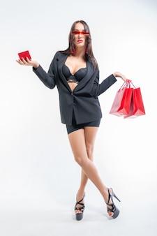Mooi sexy meisje in glazen poseren met rode pakketten en een doos voor sieraden