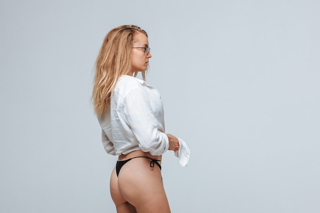 Mooi sexy meisje in zwarte bikini, wit overhemd en zonnebril op lichtgrijze achtergrond