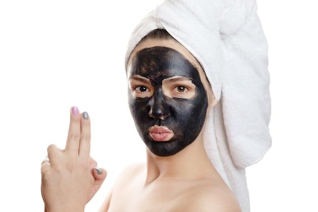 Mooi sexy meisje met zwart gezichtsmasker op de witte achtergrond, close-up portret, geïsoleerd, meisje met een handdoek op haar hoofd, zwart masker op het gezicht van het meisje, is zich overgeeft, als een crimineel