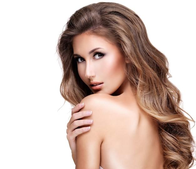 Mooi sexy model met lang bruin haar raakt haar schouder aan en kijkt ernaar. geïsoleerd op wit