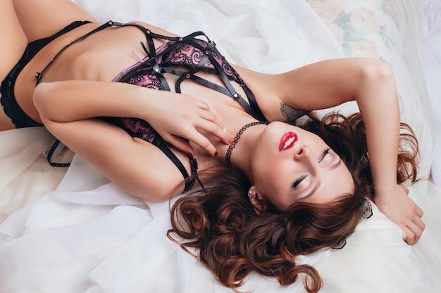 Mooi sexy naakt meisje in ondergoed met een riem op een wit bed. erotische fotoshoot charmante aantrekkelijke vrouwen
