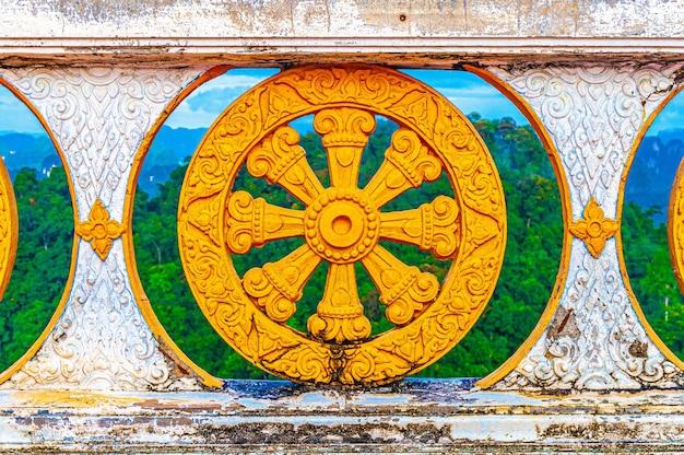 Mooi shot van de kleurrijke stenen omheining van de tempel in thailand met de bomen erachter