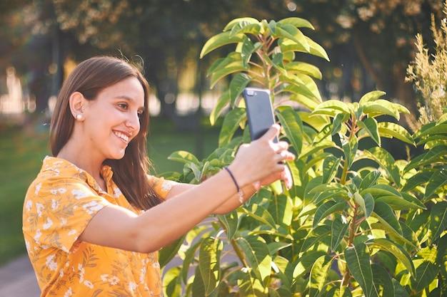 Mooi shot van een jong meisje in een geel overhemd dat een selfie naast struiken neemt