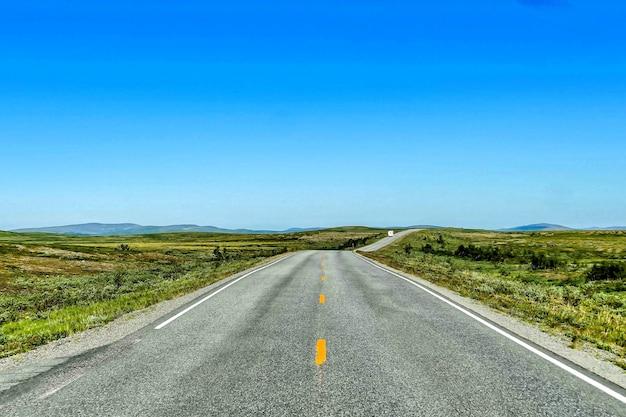 Mooi shot van een lege weg onder een blauwe hemel overdag