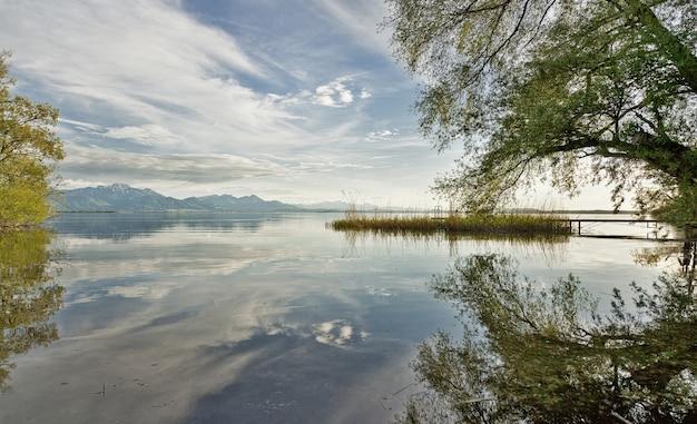 Mooi shot van een meer omgeven door bomen met heuvels