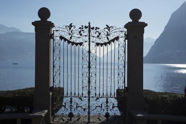 Mooi shot van een poort bij alpine lake lugano met bergen in ticino, zwitserland