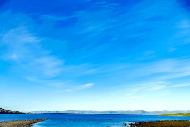 Mooi shot van een zee met bergen in de verte onder een blauwe lucht