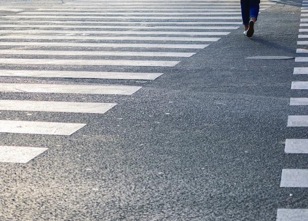 Mooi shot van het zebrapad op de weg met vrouwtje eroverheen