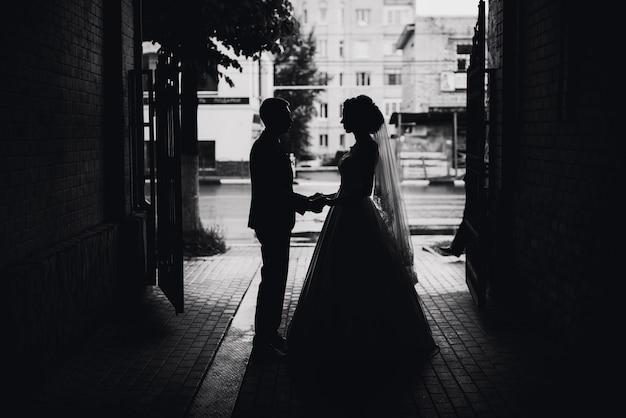 Mooi silhouet van een paar in liefdebruid en bruidegom op de huwelijksdag