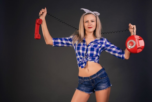 Mooi slank glimlachmeisje in een geruit blauw overhemd en een spijkerbroek houdt een oude schijftelefoon vast