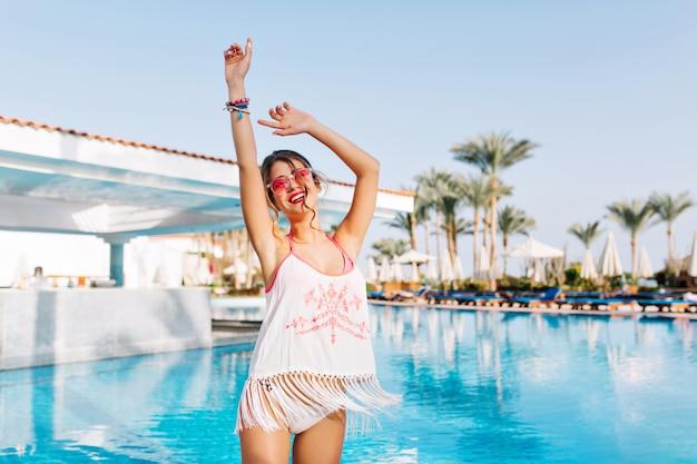 Mooi slank meisje in franje shirt en wit slipje met plezier in de buurt van het warme blauwe water met palmbomen op de achtergrond