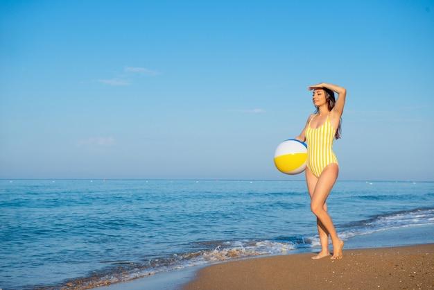 Mooi slank meisje in gele retro zwembroek staat op het strand aan zee met een opblaasbare bal in handen en kijkt in de verte.