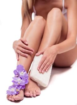 Mooi slank meisje masseert haar benen.