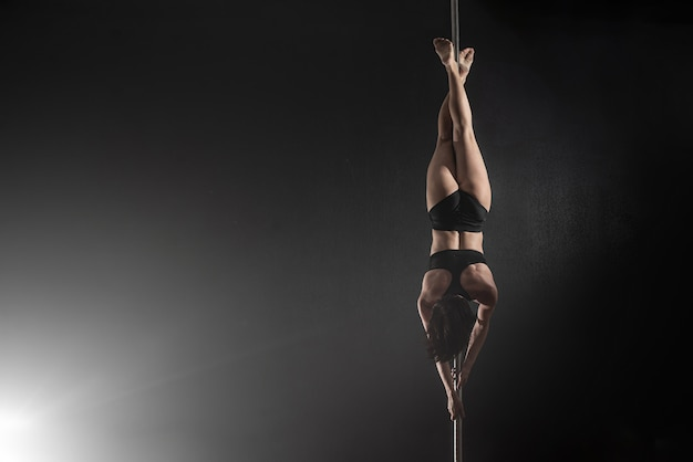Mooi slank meisje met pyloon. vrouwelijke pooldanser die op een zwarte achtergrond danst