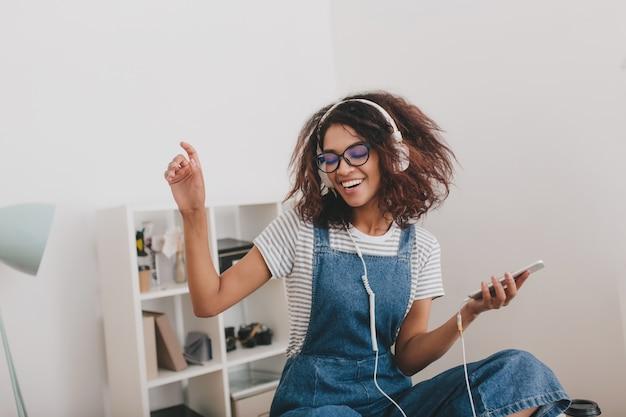 Mooi slank meisje met trendy krullend kapsel, plezier om thuis te zitten en muziek te luisteren