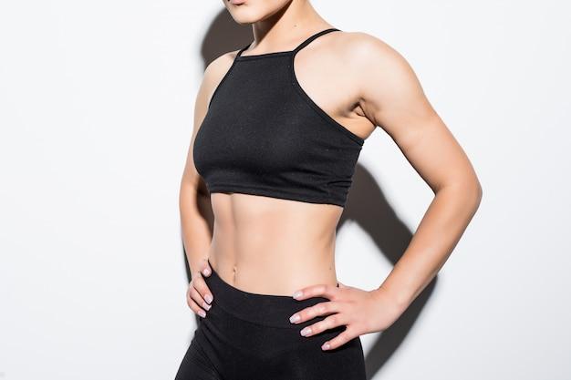Mooi slank vrouwelijk model in zwarte passende kleding die zich voordeed over wit