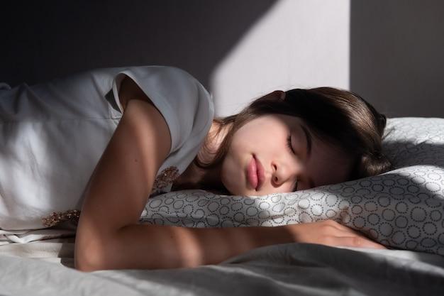 Mooi slapend meisje in de stralen van de vroege ochtendzon op haar gezicht