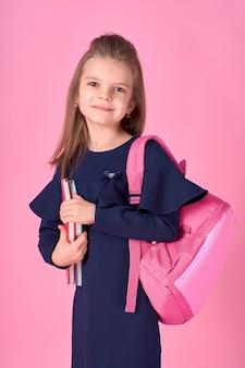 Mooi slim meisje met notebook dragen schooluniform jurk en roze heldere rugzak