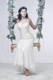 Mooi sneeuwmeisje op schommel