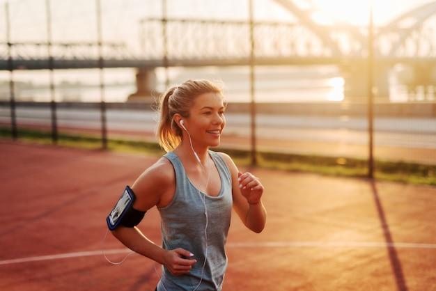 Mooi sportief geschikt blond meisje dat aan de muziek luistert en vroeg in de ochtend buiten loopt.