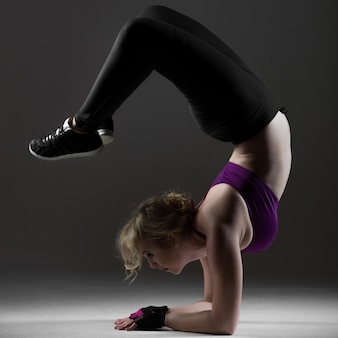 Mooi sportief meisje dat backbend op onderarmen doet
