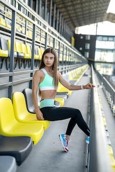Mooi sportief meisje met rust in de buurt van zit op het stadion op zonnige dag